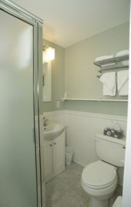 bathroom with shower, sink, and commode
