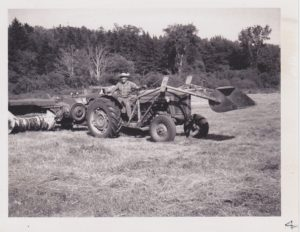 tractor and farmer in the back meadow before the inn was built
